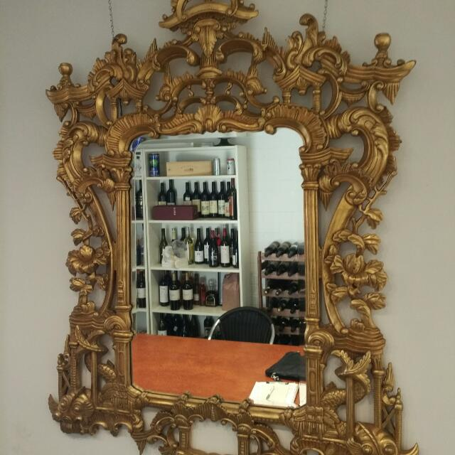 Antique Style Mirror on an Ornate Hand-carved Wooden Frame.