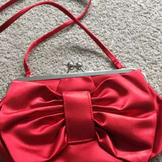 Red bow clutch sling bag