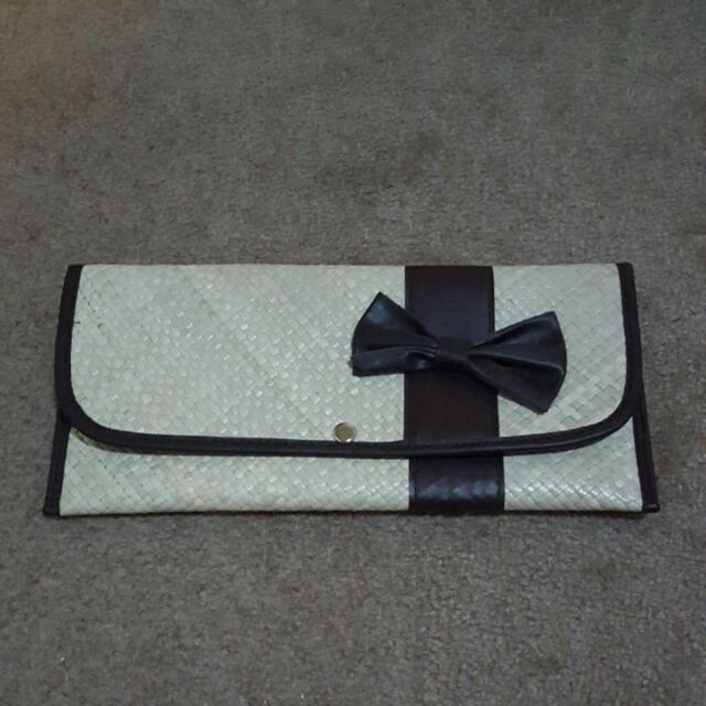 woven brown clutch with bow