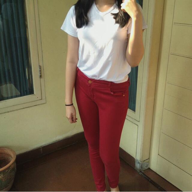 Atasan kaos putih dan celana jegging merah