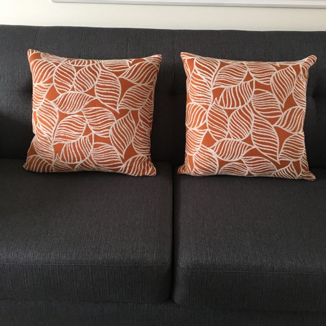 Two Orange Pillows With Leaf Design