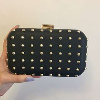 Gold studded faux leather clutch