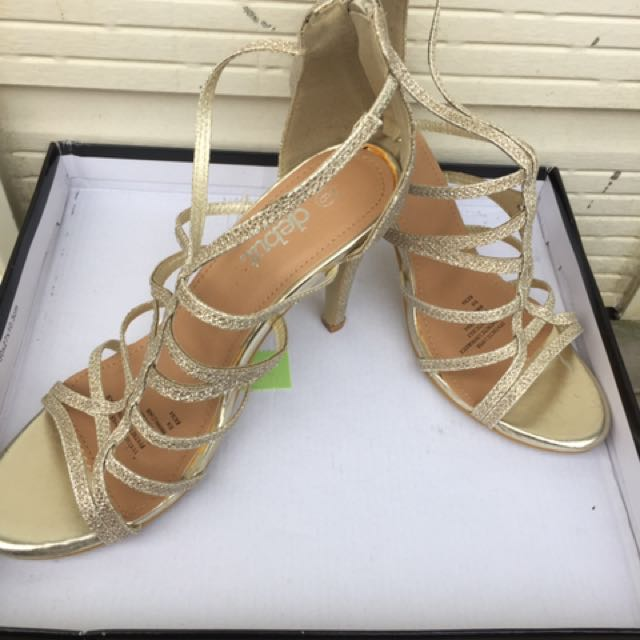 Women's pair of gold open toe ankle strap stilettos