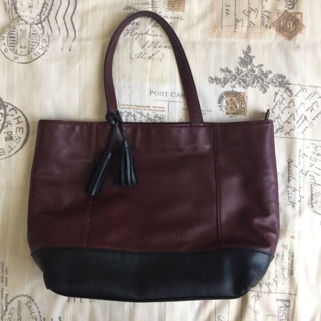 Black And Maroon Dark Red Tote Handbag Bag With Zipper And Pocket Detail And Black Tassel Detail On Strap