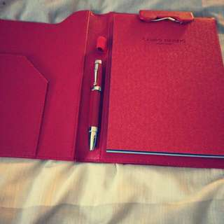A Red Italian Notebook(not Leather)/Red Pen Ensemble, Size18 x 23cm, Comes With A Matching Red Screwable Pen, Red Replaceable Note Pad And Base. When Opened The Size Is 36 x 24cm. The Pen Alone Costs More Than $100. Italian Made.