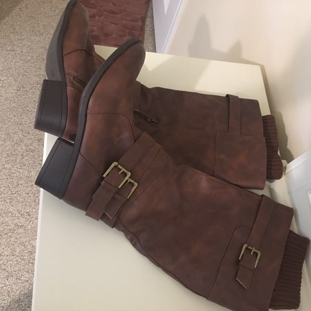 pair of brown leather buckle strap knee-high boots