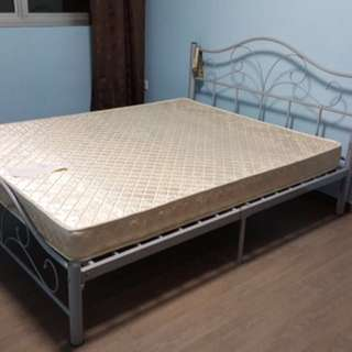 Queen size metal bed frame with mattress.