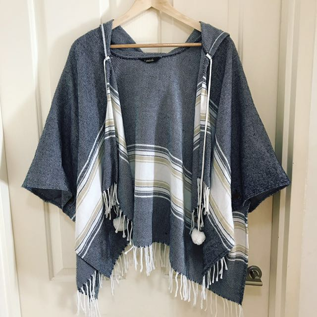 Wool poncho with hood, pom-poms and fringing