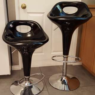 Two adjustable swivel bar stools in black.