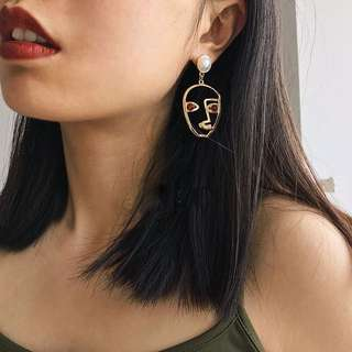 Face shaped earrings with pearl