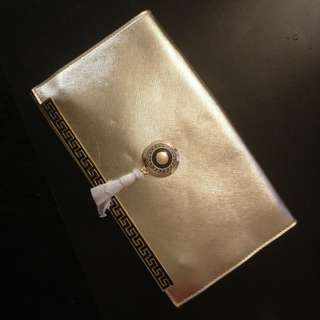 Gold convertible clutch with both wrist and long adjustable straps