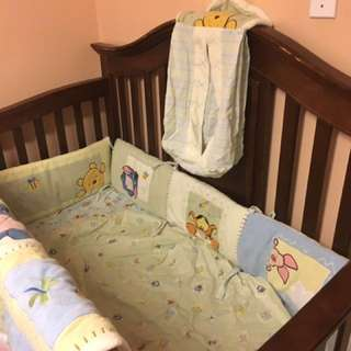 Crib set includes pooh bear bumper, fitted sheet blanket and diaper stack
