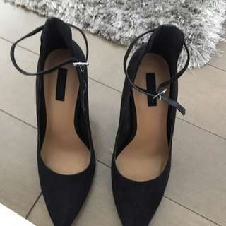 Black pointed toe high heels with ankle strap