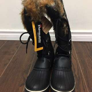 Pair of black leather brown fur top winter boots