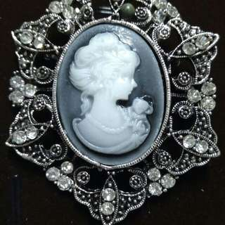Silvery brooch with cameo in silver and black combination settings with charms