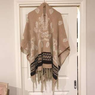 Knitted poncho/wrap with tassel detail