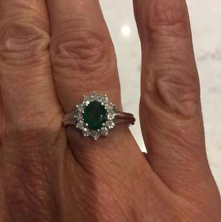 Genuine emerald ring surrounded by by diamonds set in white gold