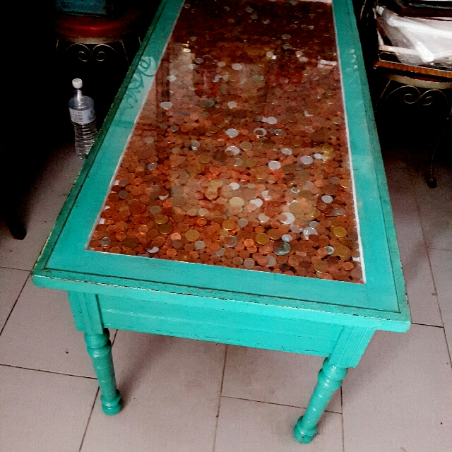 Antique coffee table with old coin