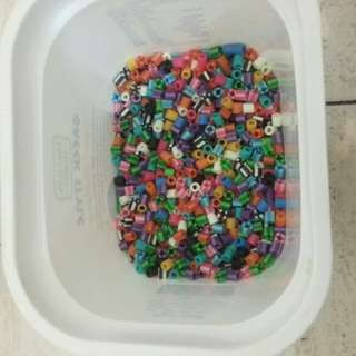 Multi - colour beads for sale ... placed in a yoghurt container