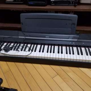 digital electronic piano with a pedal and stand