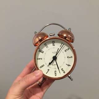Rose gold beside clock