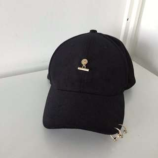 Black suede cap with gold detail and rings