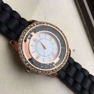 Rose gold watch with black band.