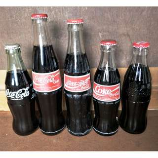 A group of Coca-Cola 5 bottles