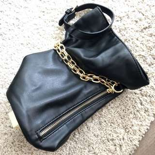 Black leather bag with golden zip and chain