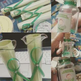 Glass invitation and small bottle with candy souvenir