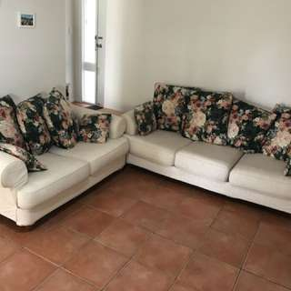 Beige couch with floral pillows. 3 seater and 2 seater