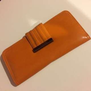 orange button fastened Boston and Bailey wallet