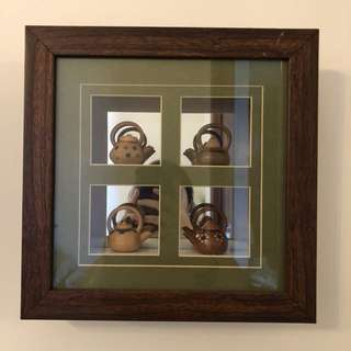 Wooden teapots in frame