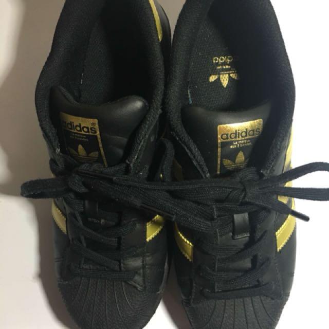 black and gold adidas superstars