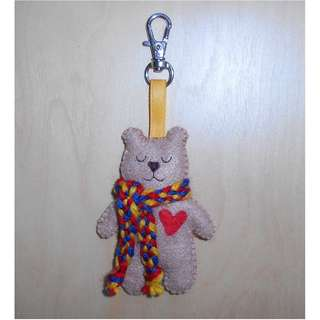 Beige bear plushie with hand-woven scarf in primary colours and lobster clasp