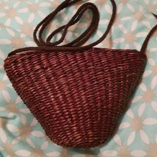 Woven hand bag with long shoulder strap.