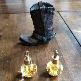 Two bottles of gold flakes and a cowboy boots