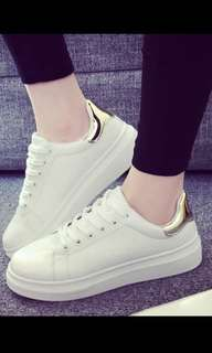 White sneakers with gold rims
