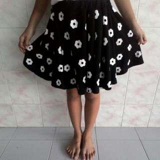 White flower in black mini skirt