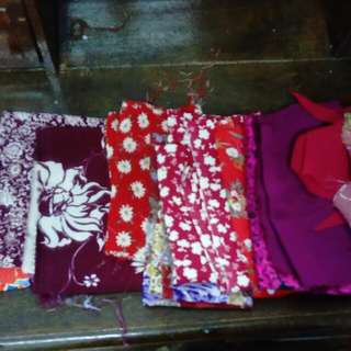 Various shades of red patterned fabric pieces