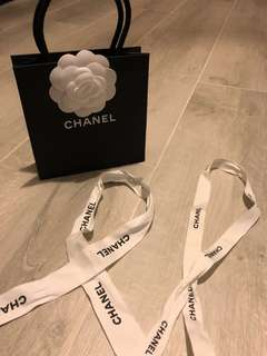 Chanel paper bag with two white ribbons (Chanel typeface on it)