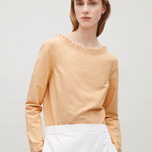 COS mustard long sleeve ruffle neck top