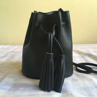 Black faux leather bucket bag with tassels