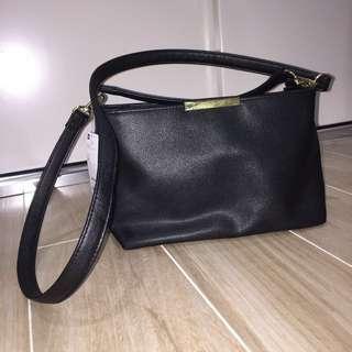 Black, gold shoulder handbag