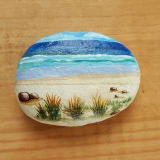 Hand painted on large pebble.  Sandy beach on sun shining day.