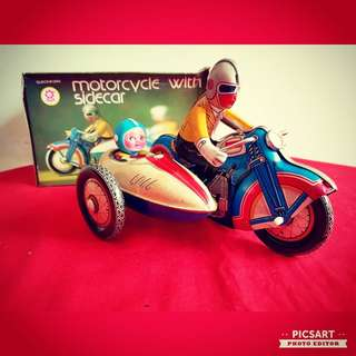 Vintage Winding Tin Toy of a Motocyle-Boat with Man riding on it and carrying a cute little boy, both with helmet. Large, size as in photo. Good Conditionand with box, working. $68, sms 96337309.