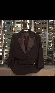 Black tuxedo with red sash n tie fm 6 years of age onwards depends on individual size.