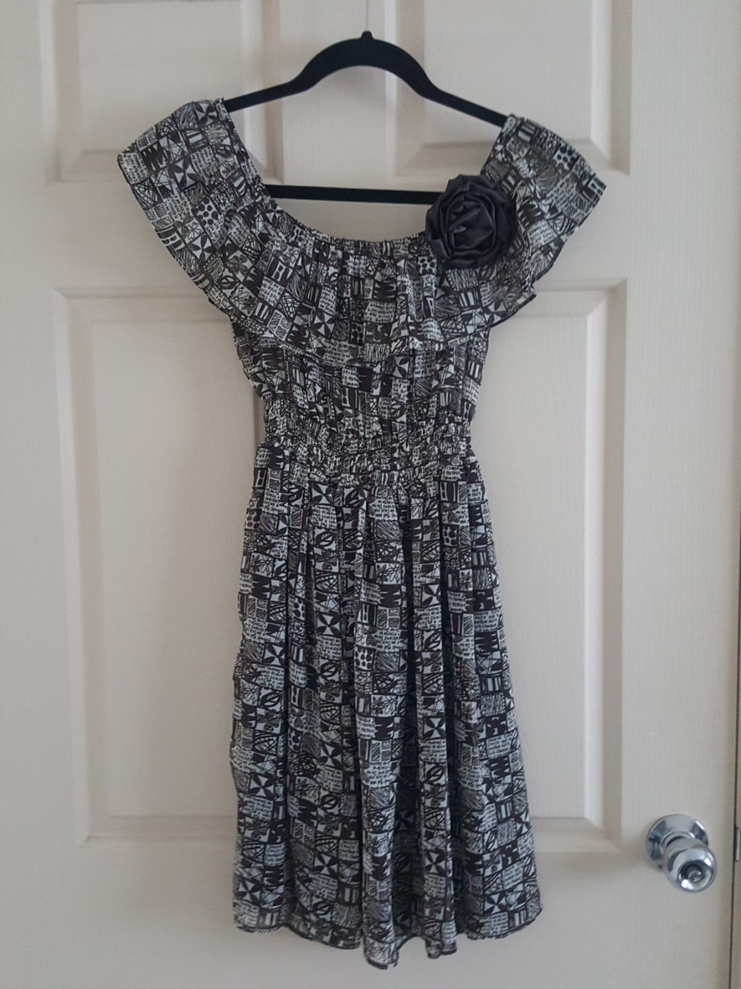 Brown patterned dress with flower brooch