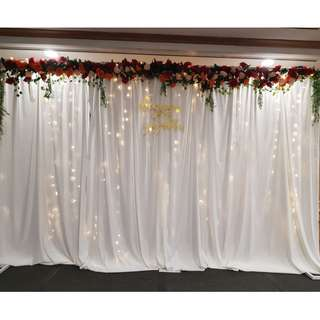 Wedding venue stage decor floral drapes with fairylights backdrop at Home Team NS
