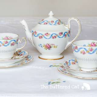 Charming tea-for-two, blue ribbon intertwined with floral swags, hard to find pattern